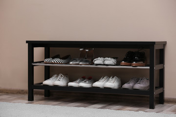 Wall Mural - Shoe rack with different footwear near color wall. Stylish hallway interior