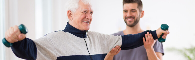 Senior man after stroke at nursing home exercising with professional physiotherapist