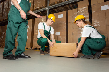 Two young warehouse workers in dark green uniforms and yellow helmets lifting heavy package