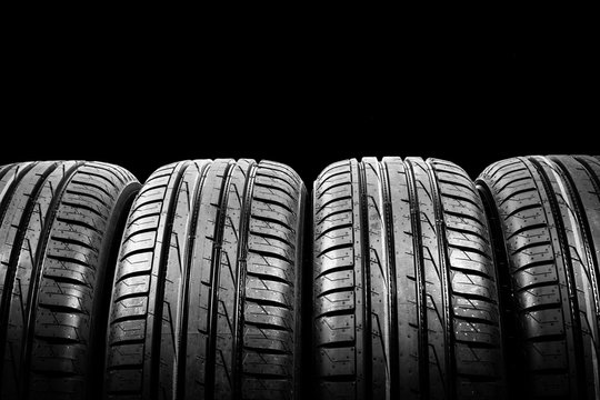 Studio shot of a set of summer car tires isolated on black background. Tire stack background. Car tyre protector close up. Black rubber tire. Brand new car tires. Close up tyre profile. Tires in a row