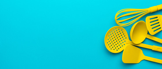 Top view photo of vivid plastic kitchen utensils. Panoramic image of yellow ladle, whisk, skimmer spoon and spatulas over turquoise blue background with copy space and right side position