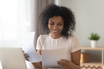 Happy african woman sit at table reading paper checking bills