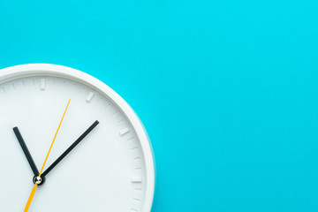 Part of white wall clock with yellow second hand hanging on wall. Close up image of plastic wall clock over turquiose blue background with copy space. Photo of time management or time is going concept