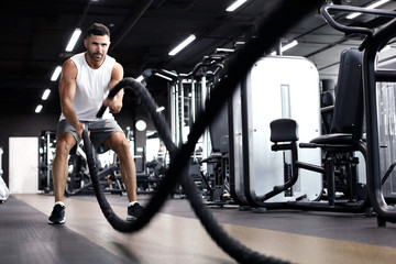 Athletic young man with battle rope doing exercise in functional training fitness gym.