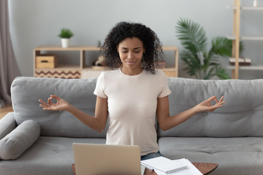 Serene african girl sit on couch meditating feel no stress