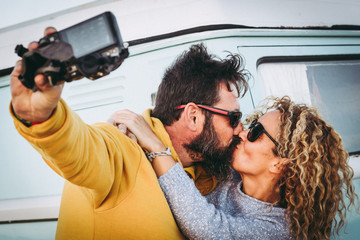 Happy kissing couple taking selfie together  with vintage van in background. Husband kiss her wife making social video with camera to share online with friends. Trends lifestyle, travel love concept.
