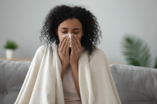 Ill african woman covered with blanket blowing nose got flu