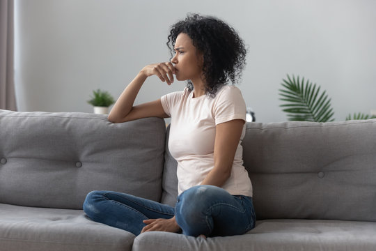 Sad thoughtful african girl on sofa looking away feel depressed