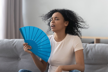 Overheated african young woman feeling hot waving fan at home Wall mural