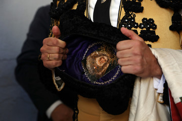 "An assistant bullfighter carries a picture of the Virgin in his ""montera"" (bullfighter's hat) before the start a bullfight at the San Fermin festival in Pamplona"