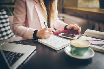 Close up caucasian woman hand on wooden table inside cafe makes notes in notebook. Subject freelancer blogger journalist at work. Unrecognizable person. Technology phone and laptop with cup coffee