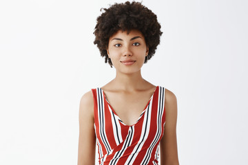 Smile a day keeps misfortune away. Portrait of cute good-looking young african american female student in striped outfit, grinning with casual carefree and relaxed expression chilling over grey wall