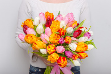 Very nice florist woman holding a beautiful colourful blossoming flower bouquet of fresh tulips...