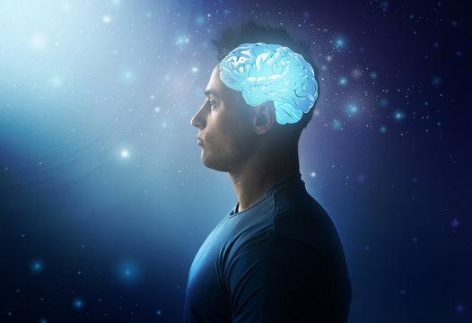 Handsome man with glowing brain on dark background