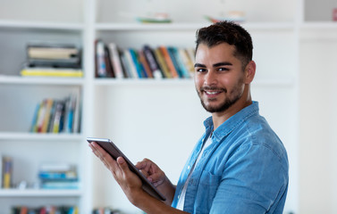 Modern mexican hipster man working with tablet computer