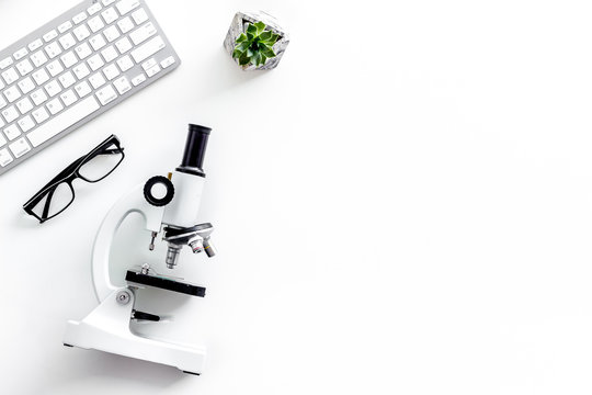 Laboratory desk with keyboard and microscope on white background top view space for text