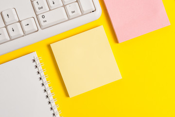 Colored empty papers with copy space on the yellow background table with pc keyboard.