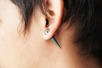 stretching ears for larger diameter tunnels,piercer hand inserts the piercing in the ear