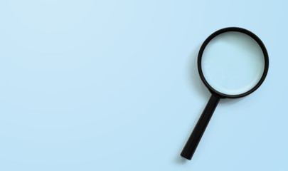 Magnifying glass on blue colour background with copy space. Searching information data concept