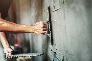 closeup hand of worker plastering cement at wall for building house Wall mural