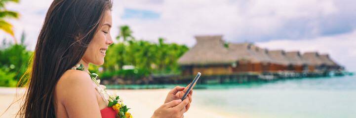 Wall Mural - Happy Asian tourist using mobile phone texting sms message on travel holiday vacation panoramic banner of luxury hotel background.