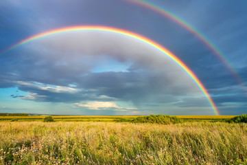 Rainbow over stormy sky. Rural landscape with rainbow over dark stormy sky in a countryside at...