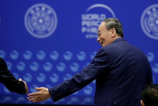 Chinese Vice President Wang Qishan shakes hands with a delegate at the opening of World Peace Forum in  Beijing