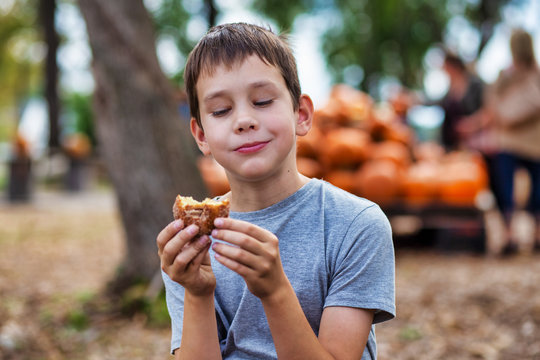 boy eating cider donut at the farm. the concept of harvest festival on the farm