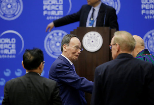 Chinese Vice President Wang Qishan shakes hands with delegates at the opening of World Peace Forum in  Beijing