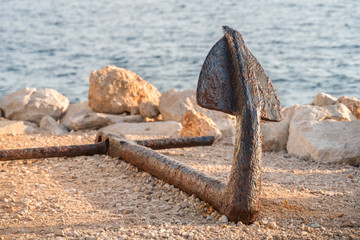 Old rusty anchor on the beach with stones