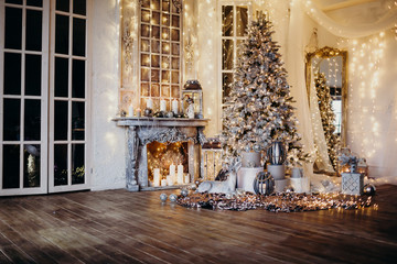 warm cozy evening in Christmas room interior design,Xmas tree decorated by lights gifts,toys, deer,candles, lanterns, garland lighting indoors fireplace.holiday.magic New year Fototapete