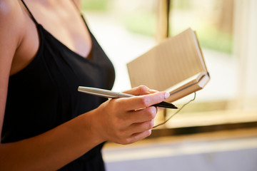 Hands of creative woman writing her thoughts and ideas in small notepad