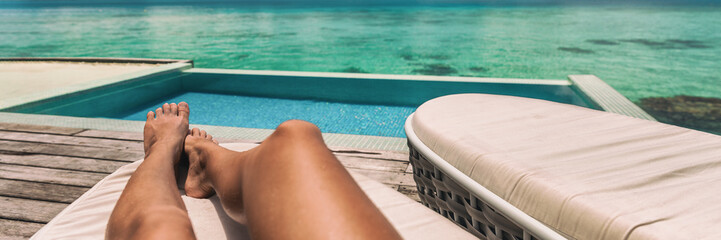 Suntan luxury vacation travel first person view panoramic of woman relaxing on sun lounger at hotel. Summer travel banner. Feet selfie beach resort background of tropical destination.