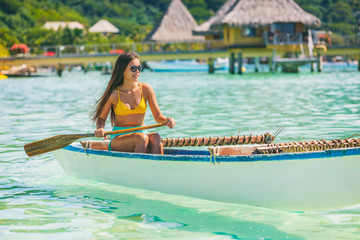Wall Mural - Outrigger Canoe polynesian watersport sport woman paddling in traditional vaa boat. Water leisure activity in Tahiti for recreation competition. Bora Bora overwater bungalow resort hotel.