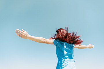 Young woman standing with raised arms on background of blue sky.
