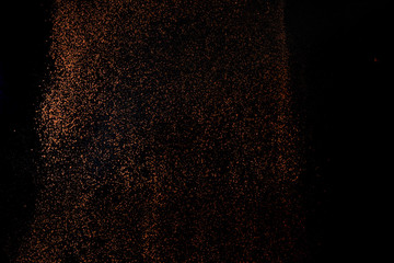 Cocoa powder sifting isolated on black background. Chocolate dust on black background.