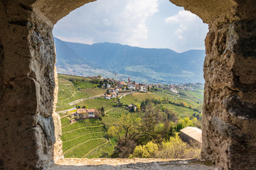 Village Tyrol, Dorf Tirol im Meraner Land, with wine plantations and Alps in background. Framed by...