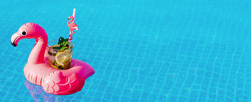 Fresh coctail mojito on inflatable pink flamingo toy at swimming pool. Vacation concept.