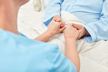 Woman holds the hands of a senior citizen in the hospice