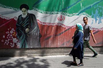 People walk in front of a mural of Iran's late leader Ayatollah Ruhollah Khomeini in Tehran