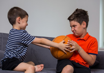 Two little kids, brothers fighting over a toy. the conflict between children over a ball