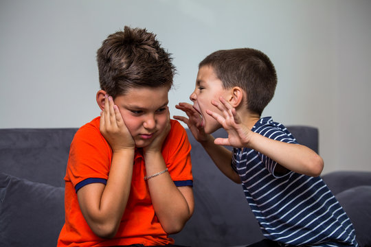 Quarreling kids - boy shouting at his brother. Child shouting loud. little child boy holding hands near head and scares his brother