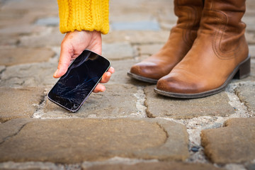 Woman picking up broken smartphone from sidewalk. Cracked touch screen on mobile phone