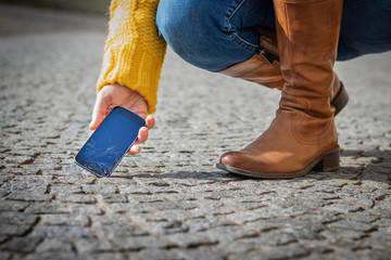 Woman picking up broken smartphone from street