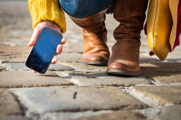 Woman picking up broken smartphone with cracked touch screen on the street