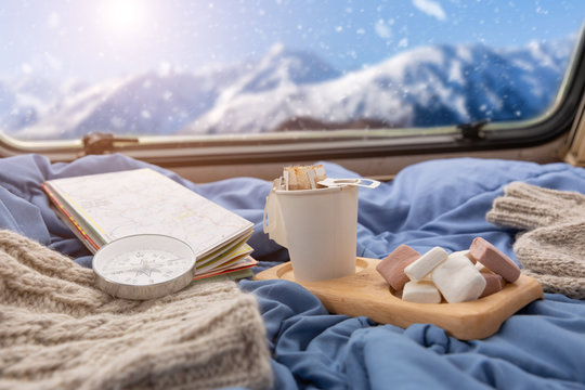 A cup of hot coffee with marshmallow near the window in the caravan camping car in the winter season,travel camping concept.