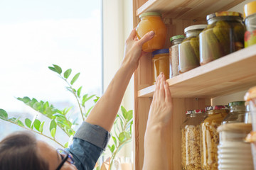 Food products in the kitchen storing ingredients in pantry. Woman taking jar of honey