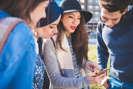 young multiracial people standing outdoor and interacting with smartphone