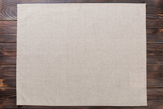 gray cloth napkin on rustic dark wooden background top view with copy space