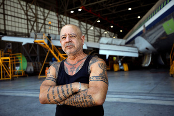 A labourer poses for a photograph next to a passenger plane as it is converted into a cargo plane at Israel Aerospace Industries site in Ben Gurion International Airport, Lod, Israel